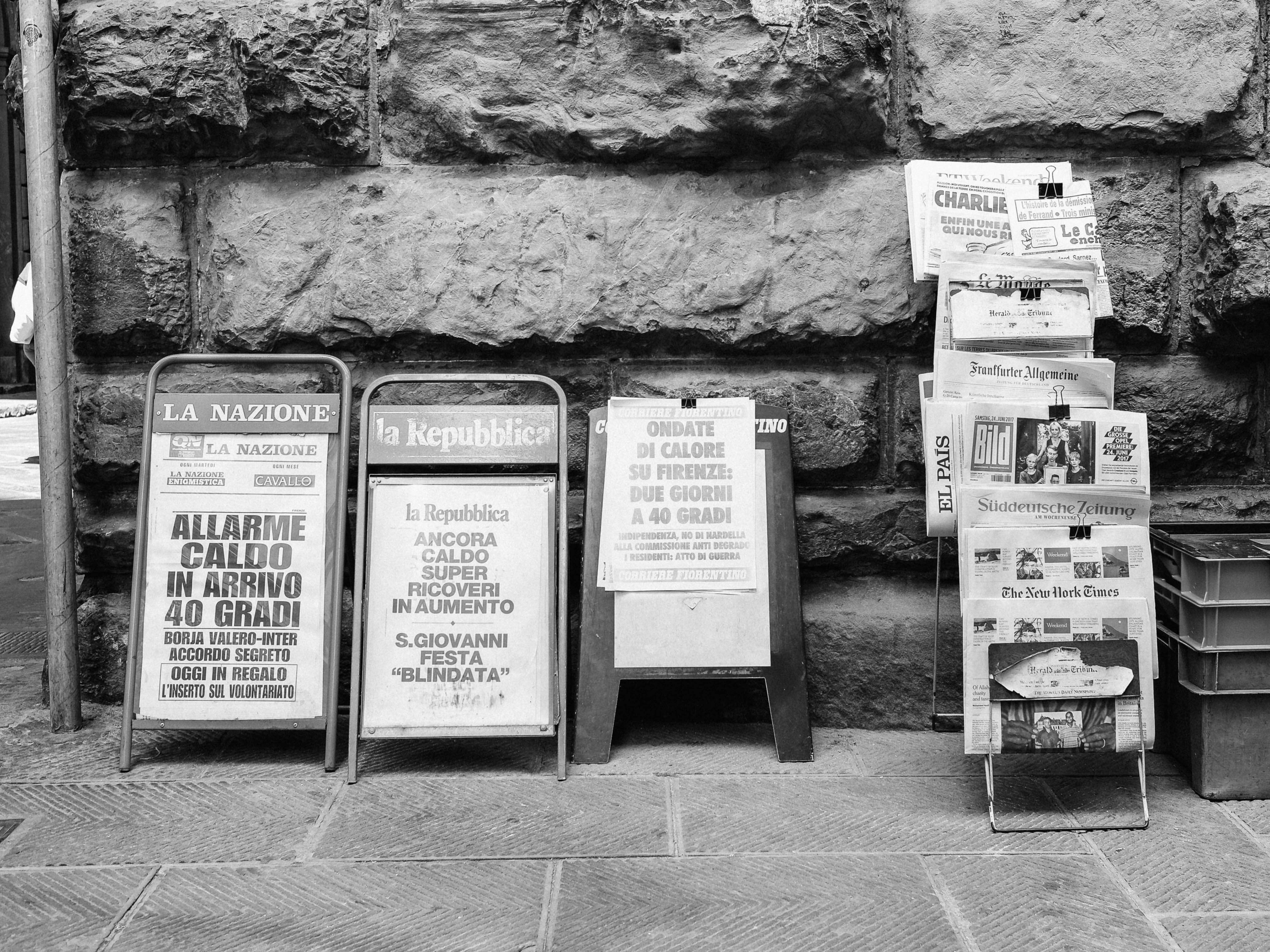 newspapers, signs, magazines on racks and displays