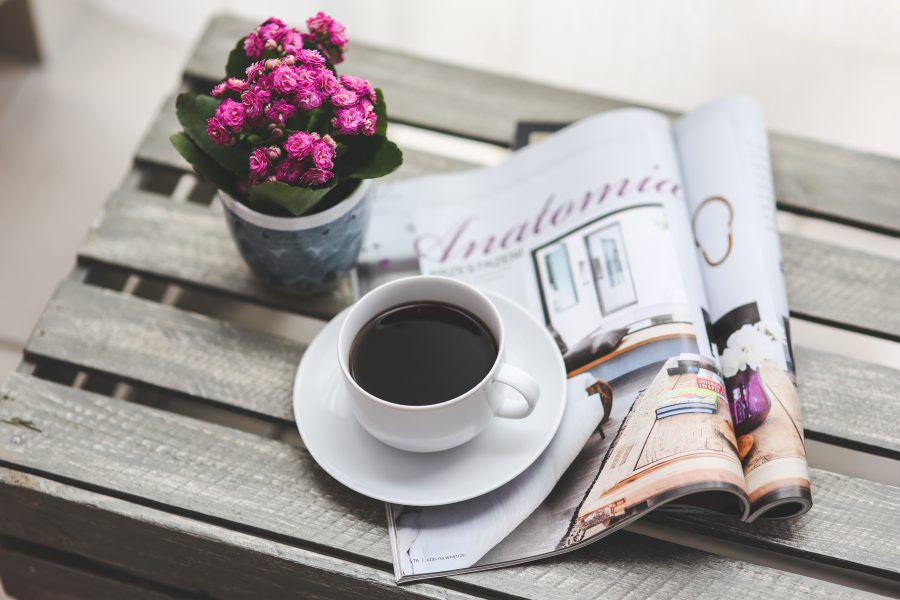 a cup of coffee, a vase of flowers and folded magazine on a wood table