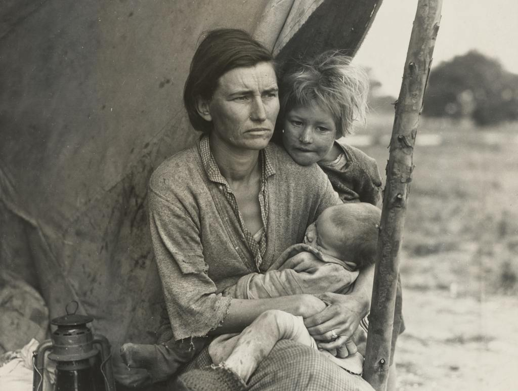 an old black and white picture of a woman with two kids in a tent