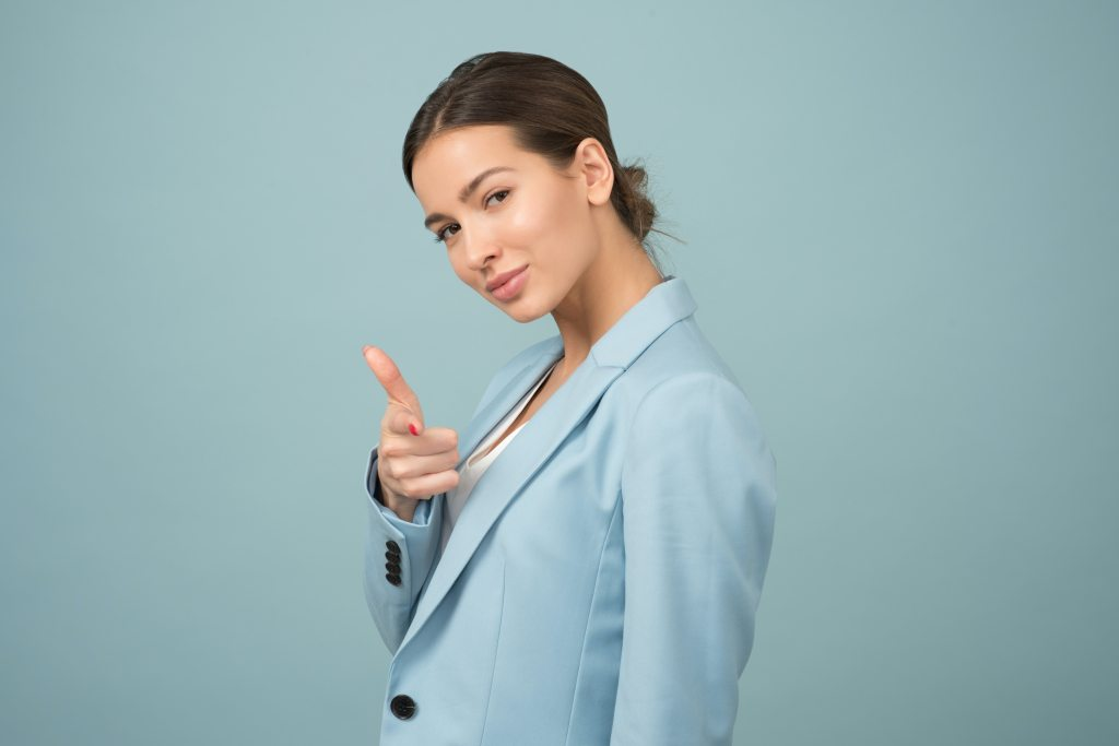 poweful woman in blue suit pointing at camera